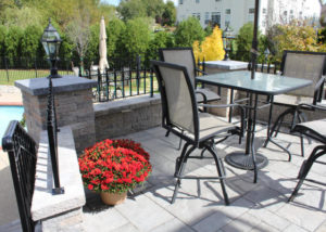 Patio table by red flowers